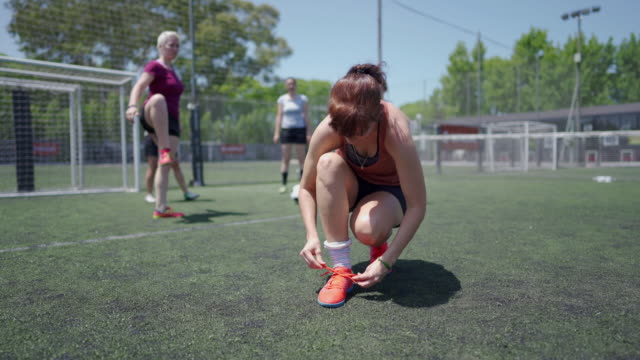 Woman soccer player tying shoelace on soccer field
