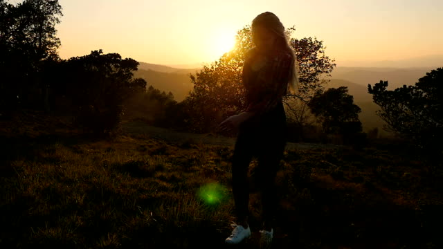Woman softly moving up on hill at sunset