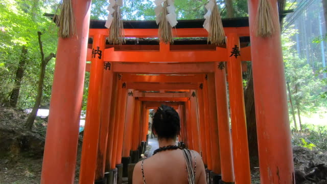woman solo traveller walking on a torii gate corridor in japan, steady shot - cultures stock videos & royalty-free footage