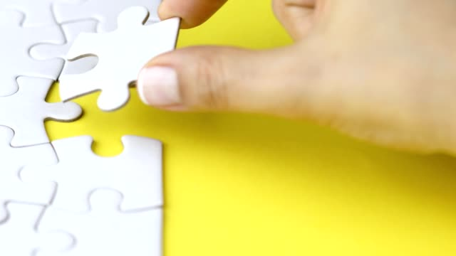 vídeos de stock e filmes b-roll de woman solving challenging jigsaw puzzle by adding last piece - the end