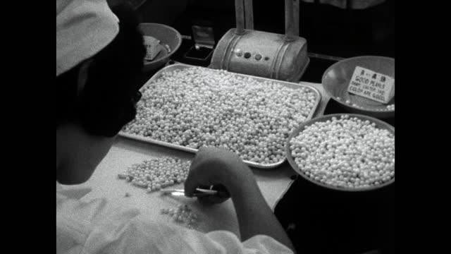 woman sorts and grades cultivated pearls by size; 1964 - workbench stock videos & royalty-free footage