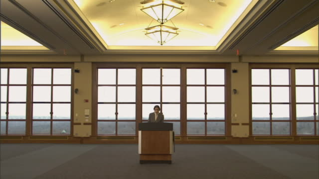 ws woman speaking at podium in conference room and walking away/ montclair, new jersey - pult stock-videos und b-roll-filmmaterial