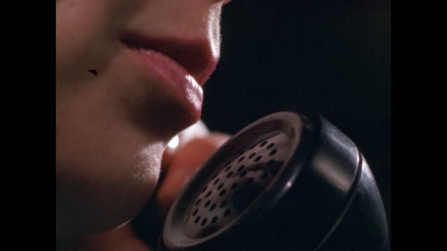 cu woman speaking into telephone receiver - 受話器点の映像素材/bロール