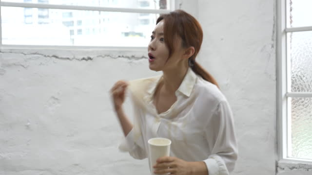 woman spilling coffee on her white shirt by colliding with someone - all shirts stock videos & royalty-free footage
