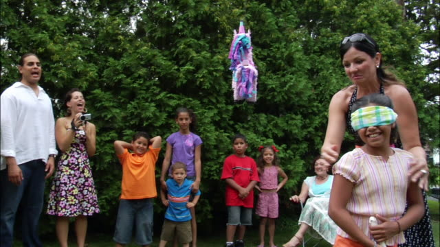 Woman spinning around blindfolded girl who prepares to hit pinata with stick / woman in background filming with digital camcorder and people watching / New Jersey