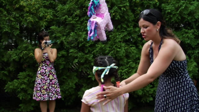 Woman spinning blindfolded girl who prepares to hit pinata with stick / woman in background filming with digital camcorder / New Jersey