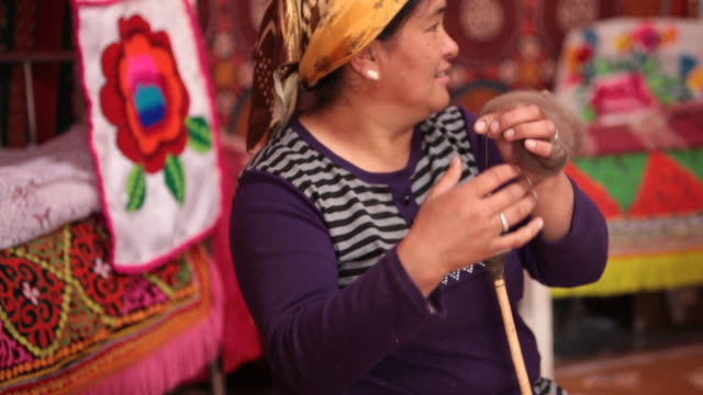 Woman spinning fiber to make yarn thread