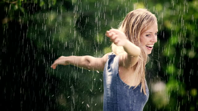 Woman spinning in summer rain