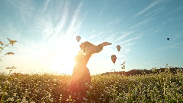 super slow motion woman spinning in the flower field in front of flying hot air balloons - dress stock videos & royalty-free footage