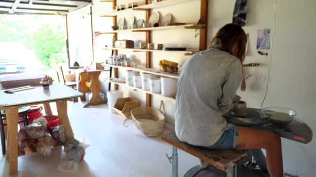 ms woman spinning mug on potters wheel in garage studio - hobbies stock videos & royalty-free footage