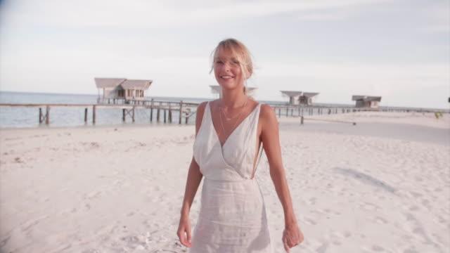 a woman spinning on a beach in a dress, traveling follow me tropical island beach. - パレオ点の映像素材/bロール