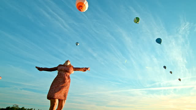 super slow motion woman spinning on the ground in front of flying hot air balloons - turning stock videos & royalty-free footage