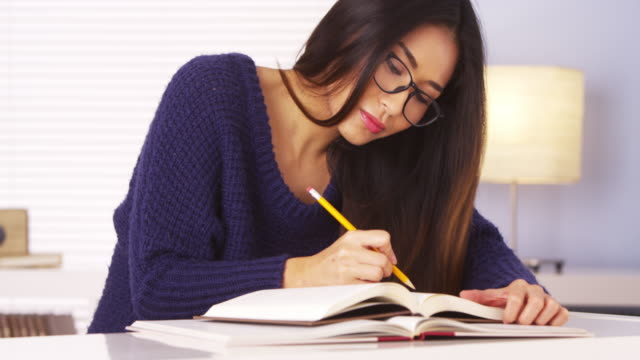 woman spinning pencil while reading book