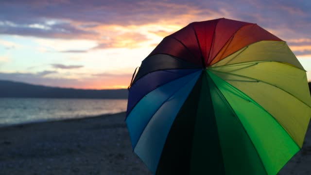 woman spinning rainbow umbrella on sand beach during sunset - multi coloured stock videos & royalty-free footage