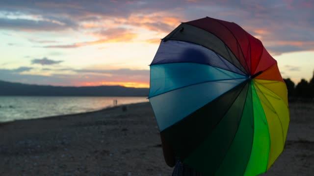 vidéos et rushes de parapluie de filature de femme arc en ciel sur la plage de sable au coucher du soleil - liberté