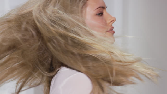woman spins and jumps creating movement in blonde hair - 人の髪点の映像素材/bロール