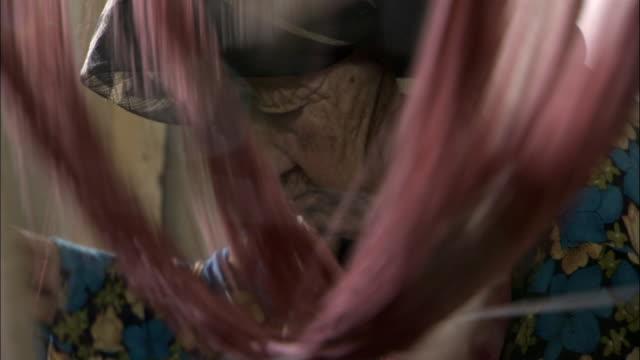 woman spins pink silk onto bobbin, hetian, xinjiang province, china - silk stock videos & royalty-free footage