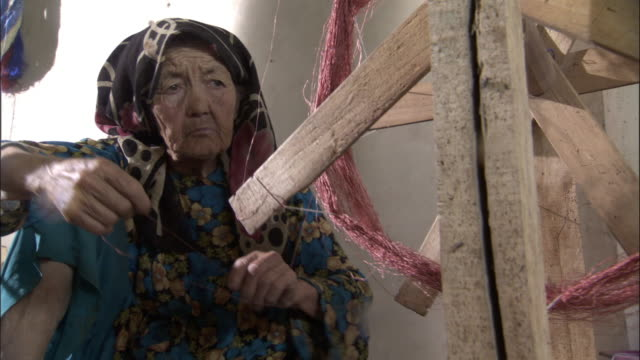Woman spins pink silk onto bobbin, Hetian, Xinjiang province, China