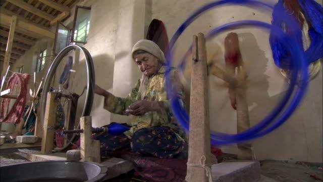 Woman spins silk, Hetian, Xinjiang, China