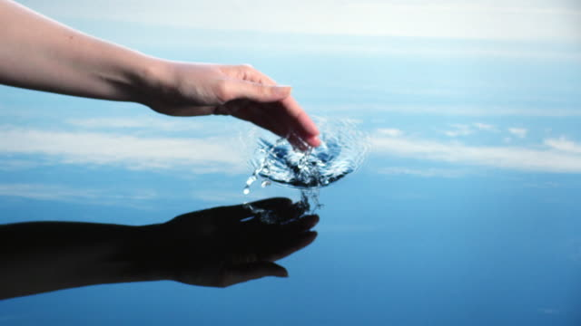 A woman splashes her hand in water to create riples reflected in a blue sky.