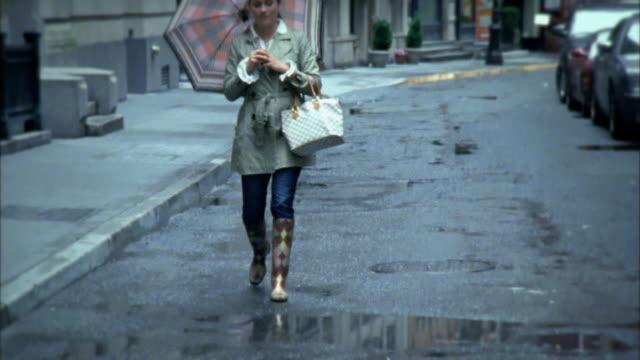 vídeos y material grabado en eventos de stock de ms tu woman splashing in puddles on street, new york city, new york, usa - paraguas