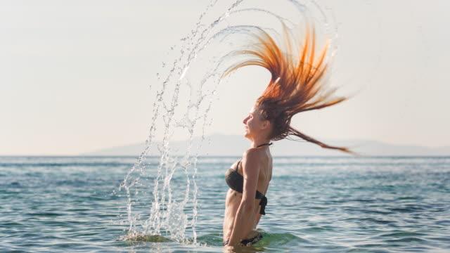 Vrouw spatten in de oceaan met lange haren