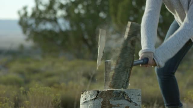 eine frau spaltet holz mit einer axt - greifen stock-videos und b-roll-filmmaterial