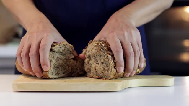 woman splitting a bread into half by hand to share - loaf of bread stock videos & royalty-free footage