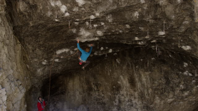 woman spotting for man rock climbing on ceiling in cave / american fork canyon, utah, united states - american fork canyon stock videos and b-roll footage
