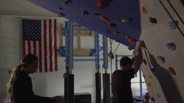 woman spotting man as he climbs rock wall in gym - arrampicata libera video stock e b–roll