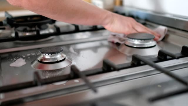 woman spraying and cleaning the oven top with a disinfectant - stove stock videos & royalty-free footage