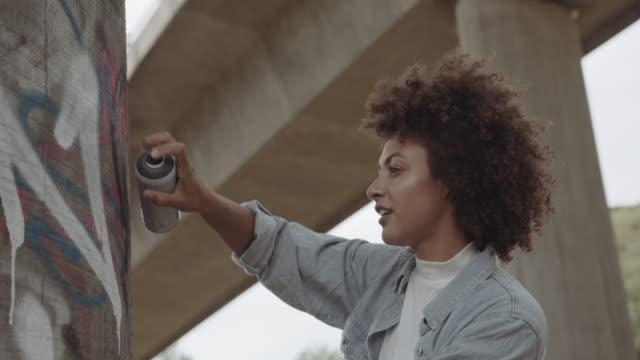 vídeos y material grabado en eventos de stock de woman spraying graffiti on concrete wall, young cool trendy black female in urban city creating graffiti street art - pared de cemento
