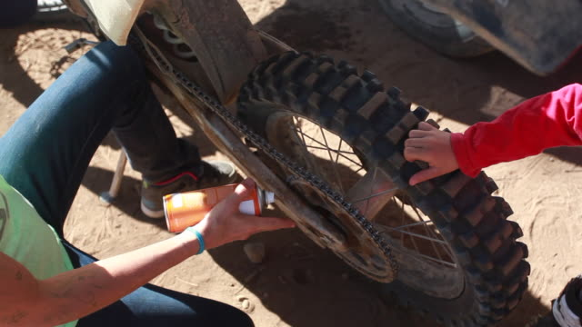 vídeos y material grabado en eventos de stock de a woman sprays a dirt bike tire while a young boy spins the back wheel - kelly mason videos