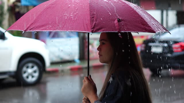 a woman spreading an umbrella in a rainy day,slow motion - below stock videos & royalty-free footage