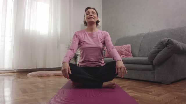vidéos et rushes de femme répandant son tapis d'exercice et s'asseyant pour faire une séance d'entraînement - assis en tailleur