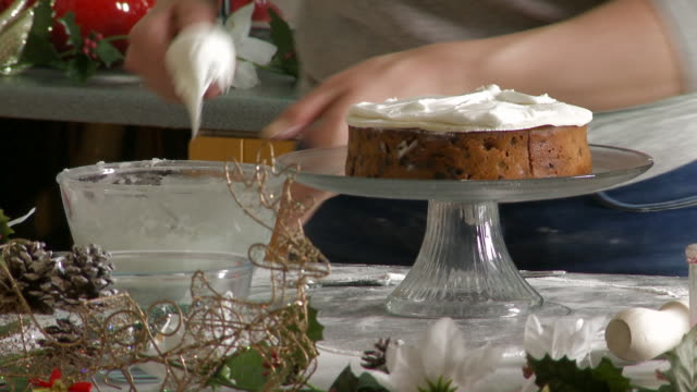 Woman Spreading Icing Over the Top of Christmas Fruit Cake