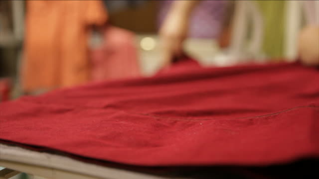 a woman spreads out an article of clothing and irons it. - ferro da stiro video stock e b–roll