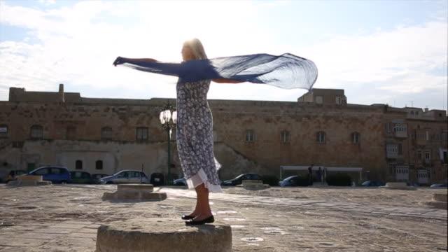 woman spreads shawl across pedestal, in piazza - バレッタ点の映像素材/bロール