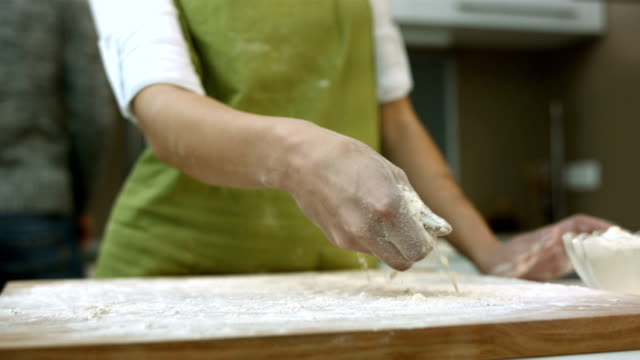 HD SLOW MOTION: Woman Sprinkling Flour Over The Board