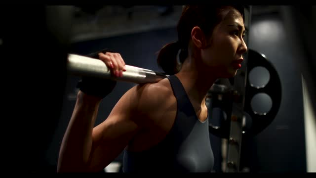 a woman squats with a barbell on her shoulder - durability stock videos & royalty-free footage