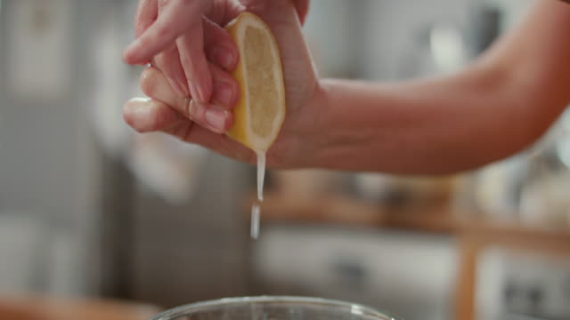 vidéos et rushes de woman squeezing fresh lemon juice into blender at home - acide ascorbique