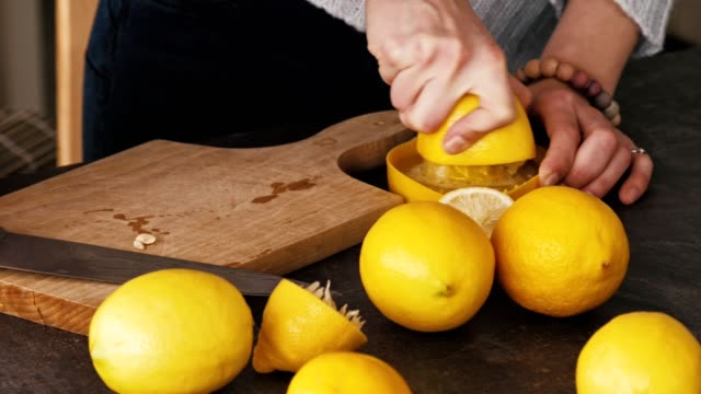 woman squeezing lemon juice in the kitchen - lemon stock videos & royalty-free footage