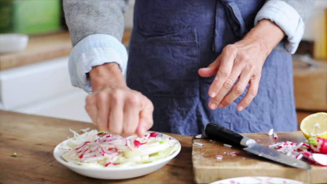 vidéos et rushes de woman squeezing lemon over cut-up radishes and fennel - assiette