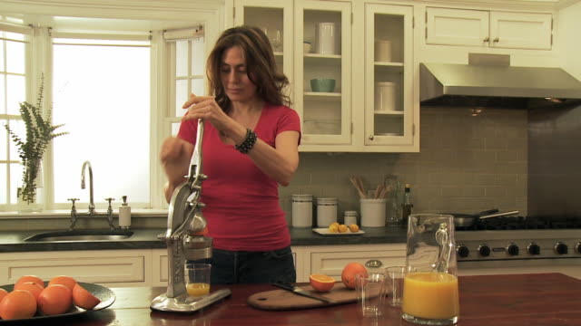 ms pan woman squeezing orange with manual press / new york city, new york, usa - juice extractor stock videos & royalty-free footage