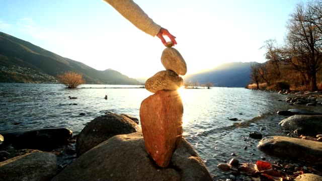 Woman stacking rocks by the lake