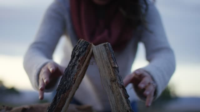 a woman stacks wood for a campfire - lumberjack stock videos and b-roll footage