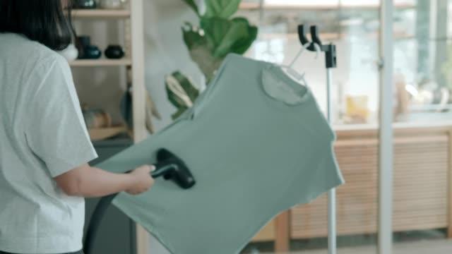 リビングルームで女性のスタンドとアイロンの服 - ストックビデオ - アイロン点の映像素材/bロール