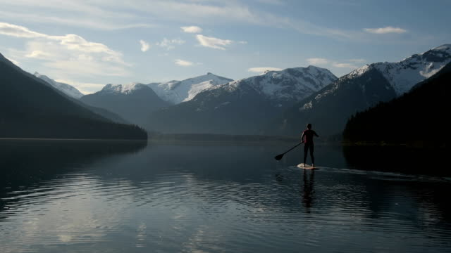 woman stand up paddle boarding on a pristine mountain lake - mountain range stock videos & royalty-free footage