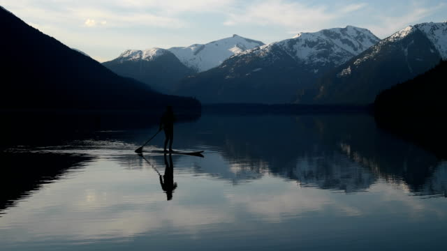 Woman stand up paddle boarding on a pristine mountain lake