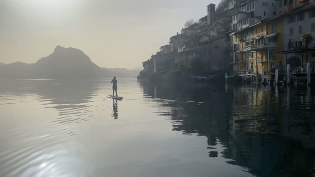 woman stand up paddle boarding sup on lake lugano past the town of gandria - one mid adult woman only stock videos & royalty-free footage